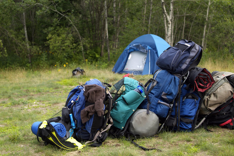Camping gear packs. Blue Backpacking bags piled up in a line at the campsite with tent in the background stock photography