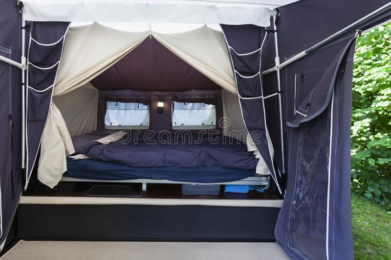 Camping or glamping bed. Camping or glamping with a real bed with mattress in a tent stock photo
