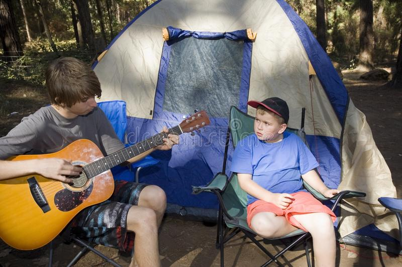 Camping and Good Guitar Music. A teenage boy playing acoustic guitar outside a tent on a camping trip royalty free stock photos