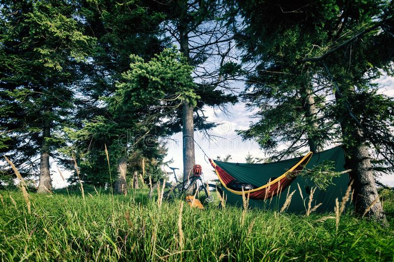 Camping with hammock in summer woods on bike travel. Camping in woods with hammock and sleeping bag on mountain biking adventure trip in green mountains. Travel stock photo