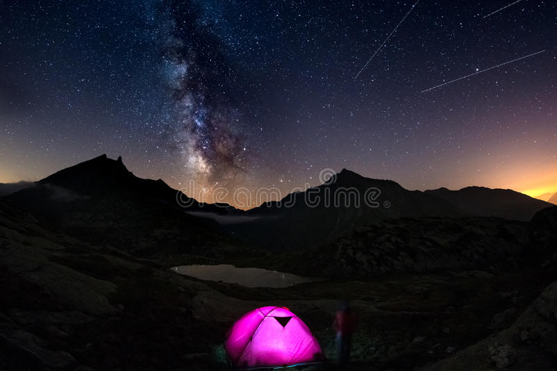 Camping with illumintaed tent at high altitude on the Alps under starry sky and milky way reflected on lake. Adventure and explora royalty free stock images
