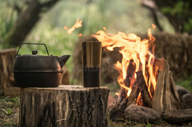 Camping items by the fire kettle with thermos stock images