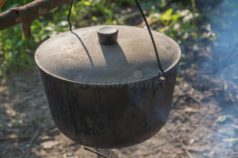 Camping kettle over the fire. Closeup. royalty free stock photography