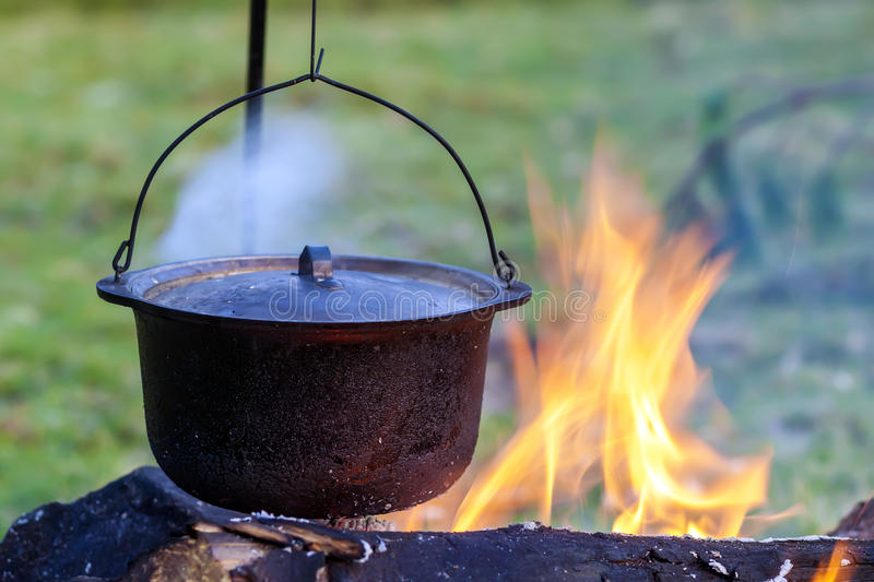 Camping kitchenware - pot on the fire at an outdoor campsite.  royalty free stock photo