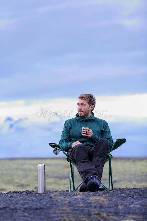 Camping man sitting in drinking coffee in nature. Camping man sitting in folding chair drinking coffee from thermos bottle flask at dusk in nature on Iceland royalty free stock photos