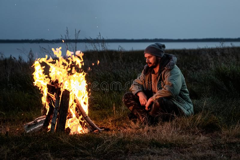 Camping man sitting by the fire at night against the sky. The concept of travel, tourism, camping royalty free stock photos