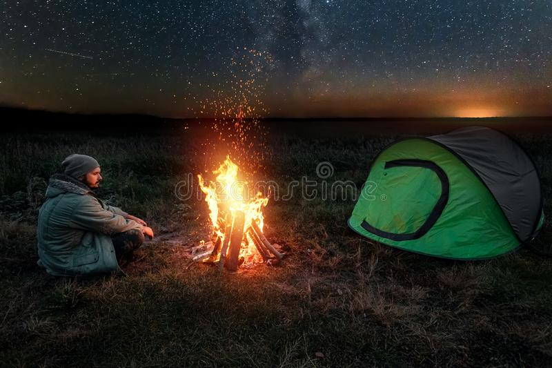 Camping man zit 's nachts bij het vuur tegen de achtergrond van de sterrenhemel Reis, toerisme, kamperen stock fotografie