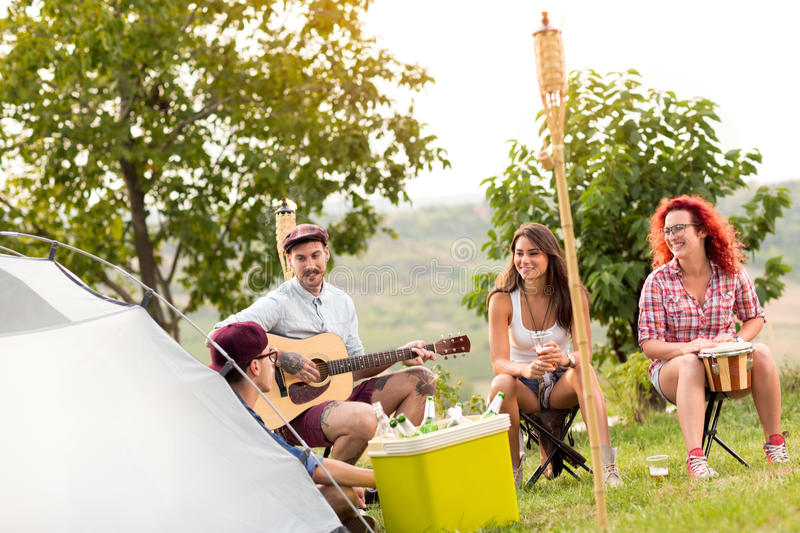 Camping in nature. Group of youngsters camping in beautiful nature stock photography