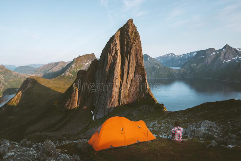 Camping in Norway man traveler relaxing in mountains with tent. Travel adventure healthy lifestyle active summer vacations sunset Segla mountain peak view stock photography