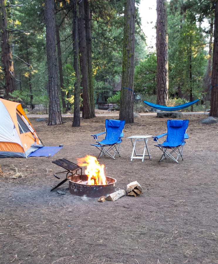 Campsite in the woods with a tent,two chairs, hammock and a burning firepit. stock photos