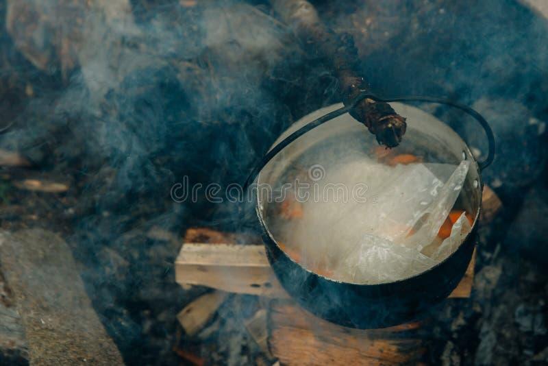 Camping rapproché au-dessus d'un feu de camp, casserole de soldat, cuisine dans les bois, avec la forêt tropicale sur fond image stock