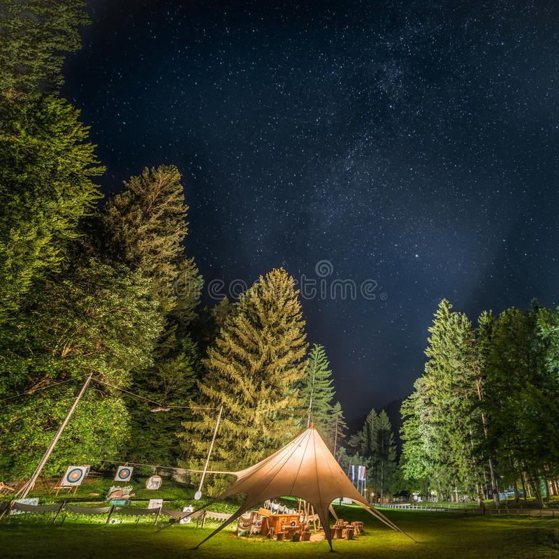 Camping Shelter at Starry Night Surrounded by Trees stock images
