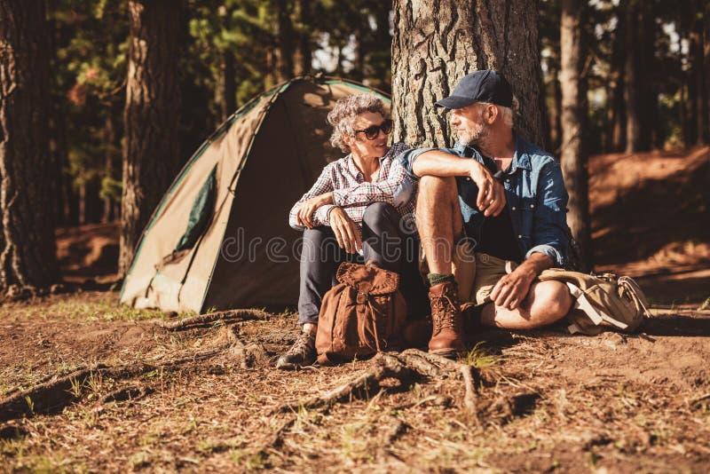 Camping supérieur heureux de couples dans la forêt image libre de droits