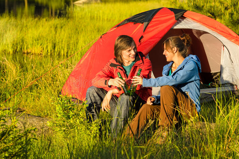 Camping teenagers drink beer outdoors. Sunset on the meadow royalty free stock images