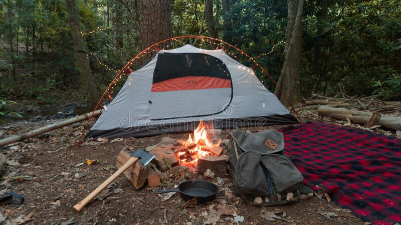 Camping tent in the Blue Ridge Mountains in Asheville, North Carolina. Outdoor lifestyle with axe, cast iron skillet, flannel blan stock photo