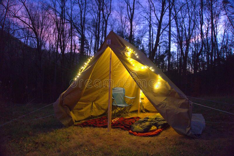 Camping tent in the Blue Ridge Mountains in Asheville, North Carolina. Outdoor lifestyle with axe, cast iron skillet, flannel blan royalty free stock image