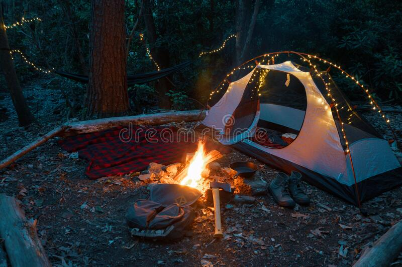 Camping tent in the Blue Ridge Mountains in Asheville, North Carolina. Outdoor lifestyle with axe, cast iron skillet, flannel blan stock photos