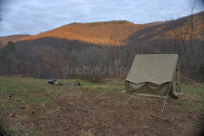 Camping tent in the Blue Ridge Mountains in Asheville, North Carolina. Outdoor lifestyle with axe, cast iron skillet, flannel blan royalty free stock images