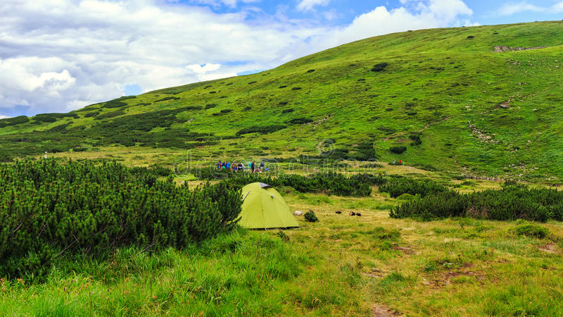 Camping tent and in the distance group of people at Carpathian mountains, summertime journey. royalty free stock photography