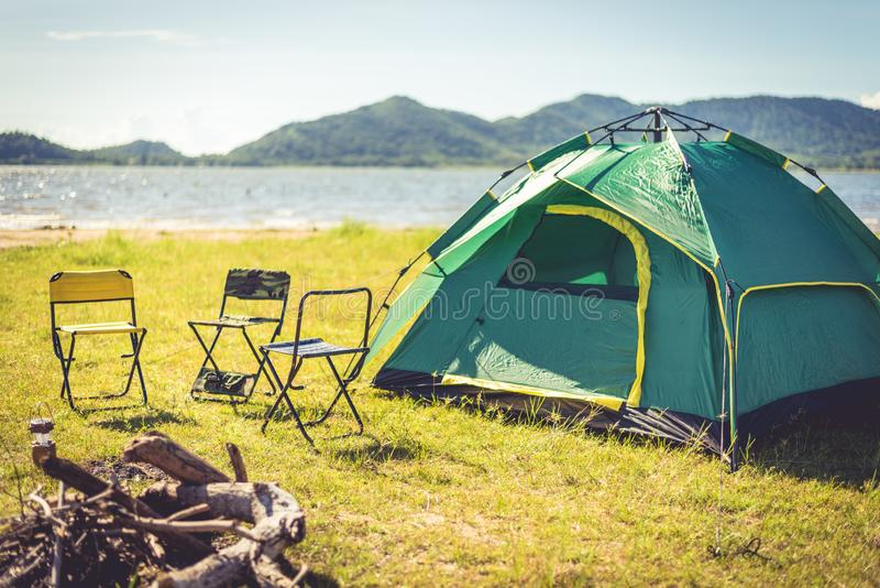 Camping tent with extinguished bonfire in the green field meadow, Lake and mountain background. Picnic and travel concept. Nature. Theme stock photos