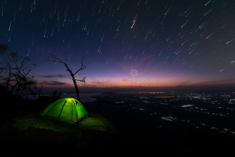 Camping tent glows on mountain under a night sky, background sta royalty free stock photography