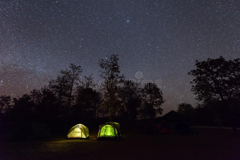 Camping tent glows under a night sky full of stars royalty free stock photos