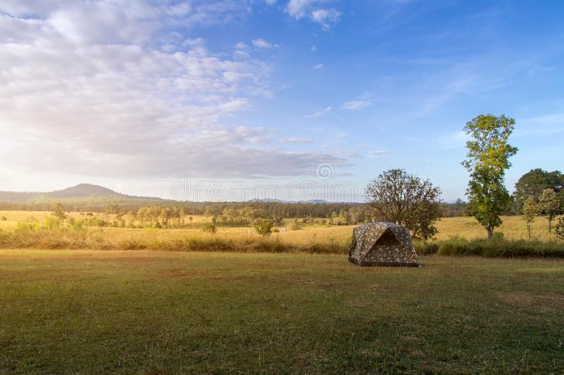 Camping tent on green field near forest during dramatic sunrise at summer misty morning,Concept of outdoor camping adventure stock image