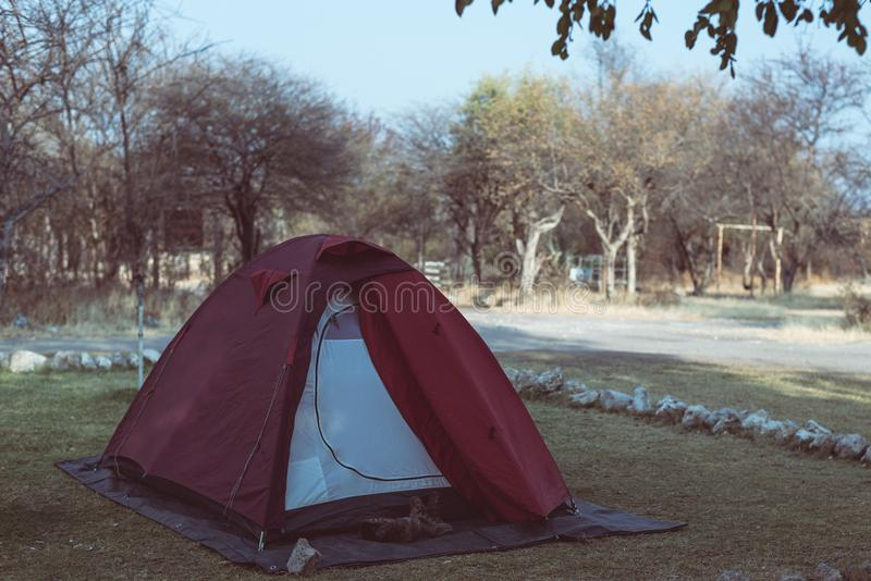 Camping tent and hiking boots. Adventure traveling and outdoor activities in Africa. Toned image, vintage style. Camping tent and hiking boots. Adventure stock images
