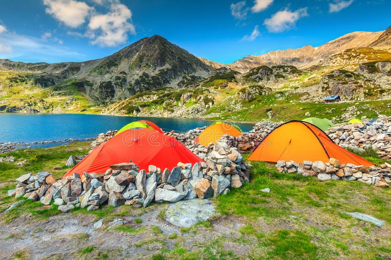 Camping and tent near alpine lake in the mountains, Romania. Wonderful alpine camping place with colorful tents near Bucura glacier lake. Stunning mountain stock image