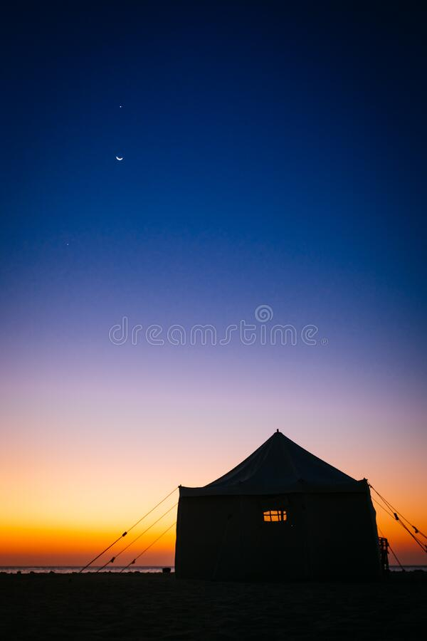 Camping Tent Near Sea Under Blue Sky during Sunset stock image