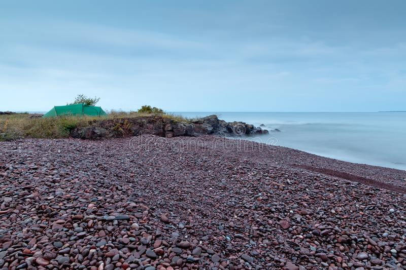 Camping on the Lake Superior shore. Camping tent, rocky shore and endless water going into horizon royalty free stock photos