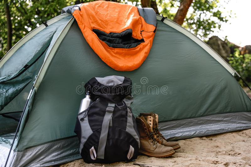 Camping tent with sleeping bag, boots and backpack royalty free stock images