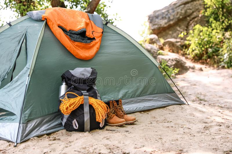 Camping tent with sleeping bag, boots and  on beach stock images