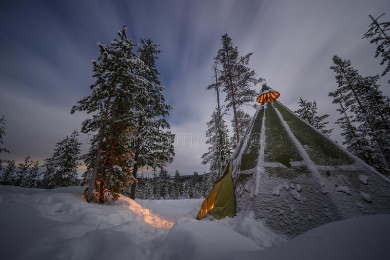 Camping tent in the snow forest with fire light in a cold winter in Finland royalty free stock photos