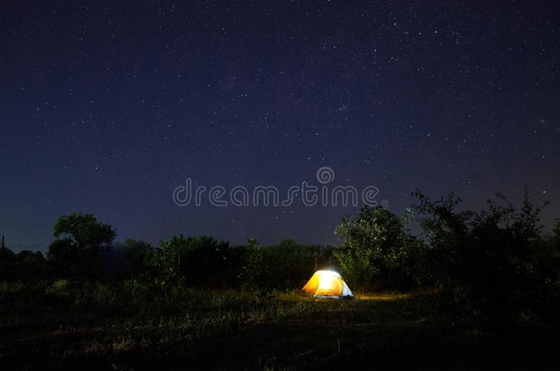Camping tent under beautiful night sky full of stars. Starry night sky above illuminated touristic tent royalty free stock image