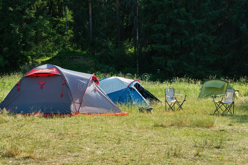 Camping tents and folding chairs in forest royalty free stock photo