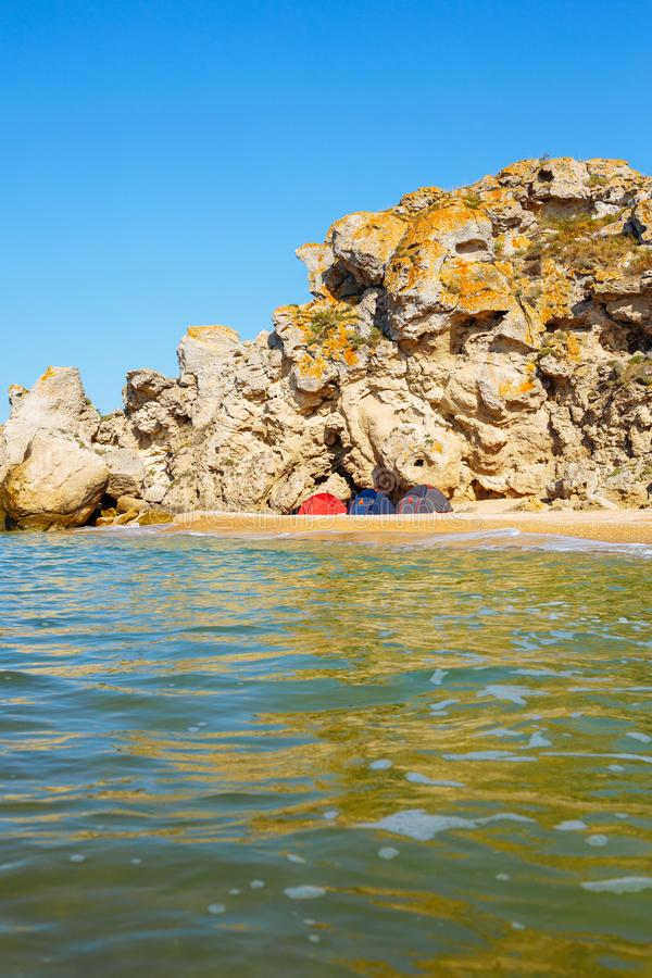 Camping of three tents on a sandy wild beach stock images