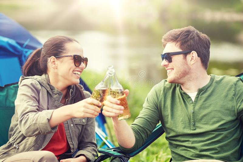 Happy couple clinking drinks at campsite tent. Camping, travel, tourism, hike and people concept - happy couple clinking beer bottles at campsite tent stock image