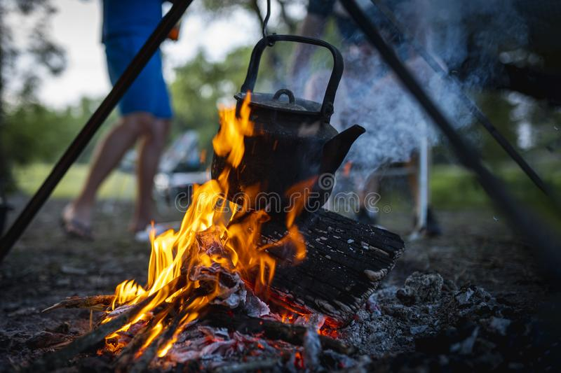 Camping trip. kettle is heated over the fire stock image