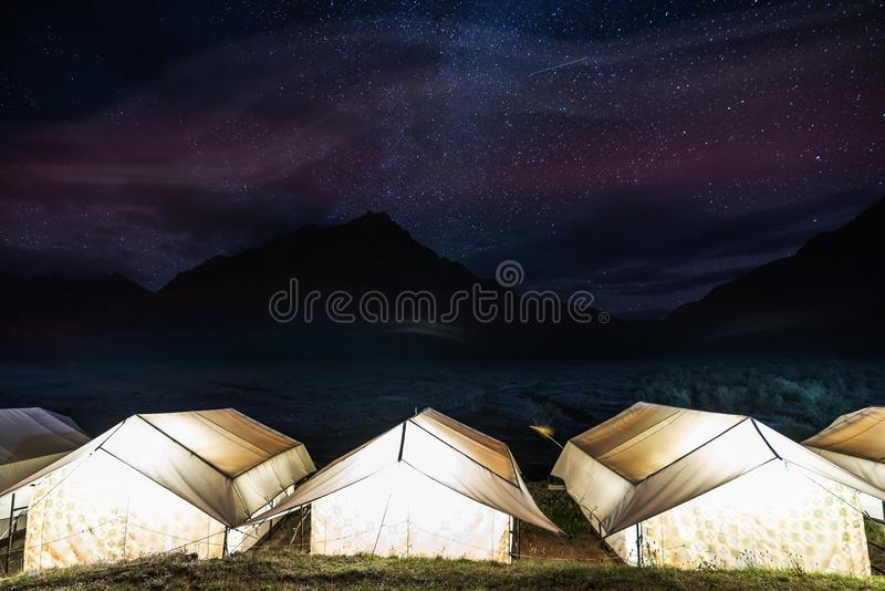 Camping under colourful sky full of stars. Glowing tents with silhouette mountains and sky full of star at Rangdum Monastery in In stock photography