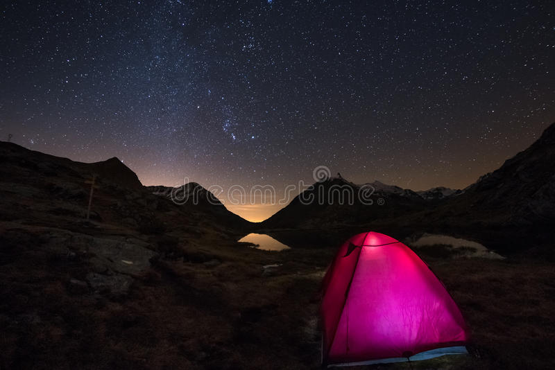 Camping under starry sky and Milky Way arc at high altitude on the italian french Alps. Glowing tent in the foreground. Adventure stock image