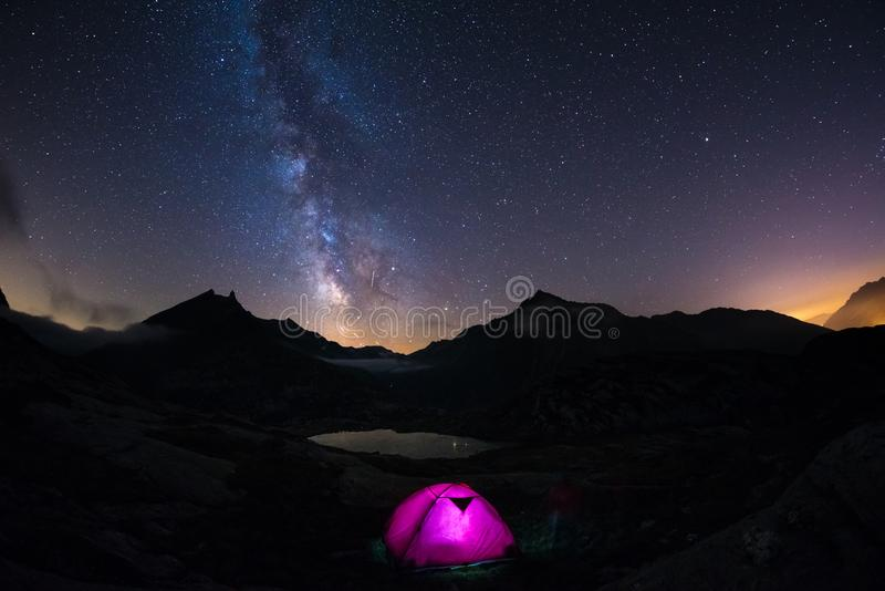 Camping under starry sky and milky way at high altitude on the Alps. Illuminated tent in the foreground and majestic mountain peak stock images