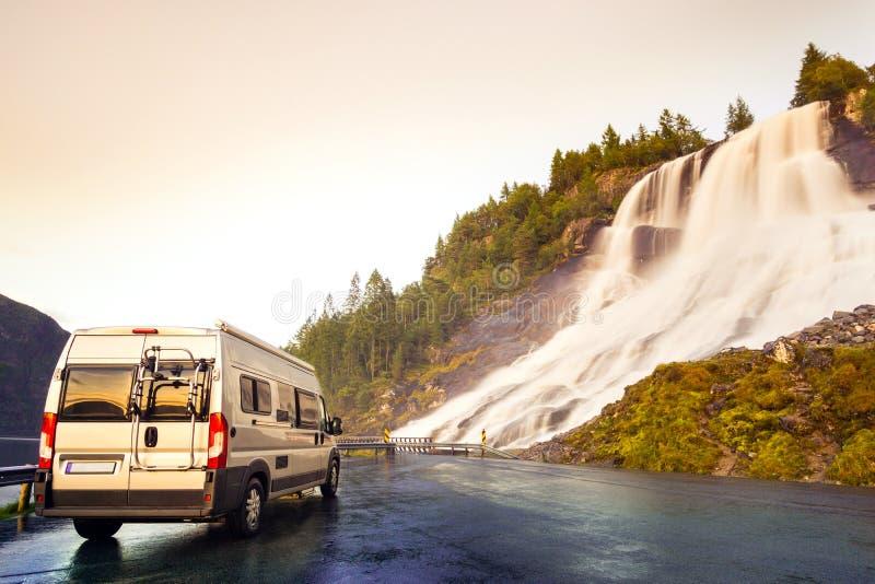 Camping van at beautiful huge waterfall. Amazing cataract at road in sunset light. Norway. stock photos