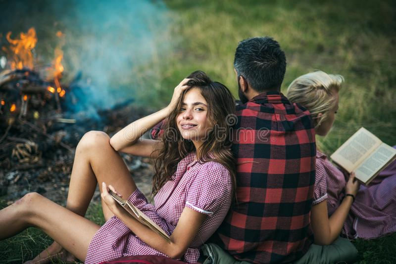 Camping in wilderness. Turn back guy looking at fire while two beautiful girls read book. Smiling brunette with braces stock images