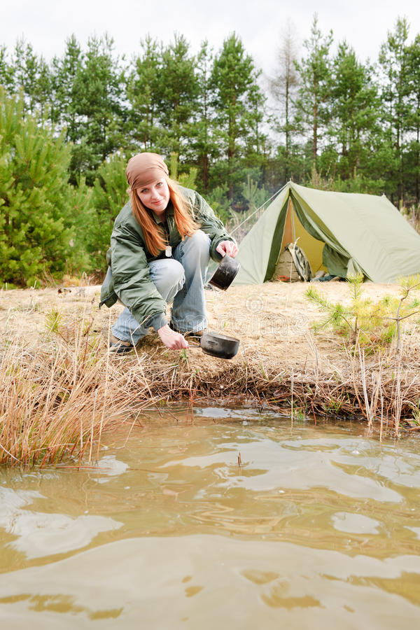 Camping woman tent washing dishes nature stock photo