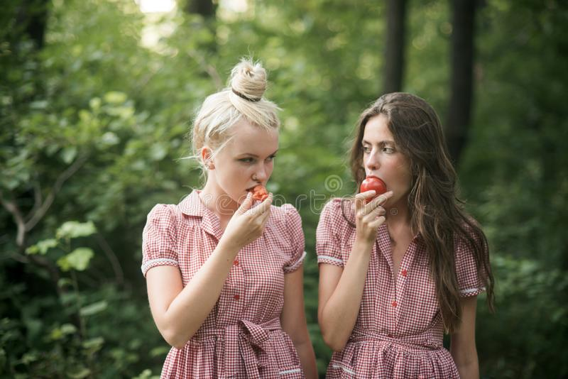 Camping in woods. Beautiful young girls wandering in forest. Two sisters in vintage dresses eating juicy tomatoes stock photo