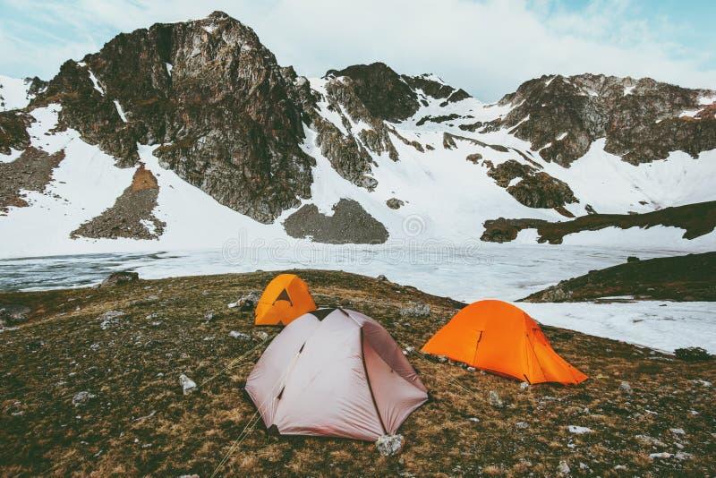 Campingowi namioty w górach przy zamarzniętym jezioro krajobrazem obrazy stock
