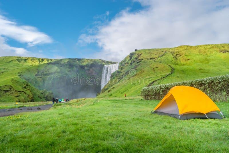 Campingplats med tält framför den berömda Skogarfoss-vattenfallet, när man vandrar på Island, sommaren arkivfoto