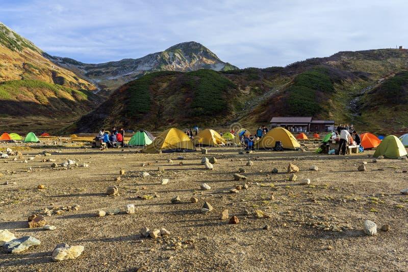 Campingplats och få färgrika tält arkivbilder
