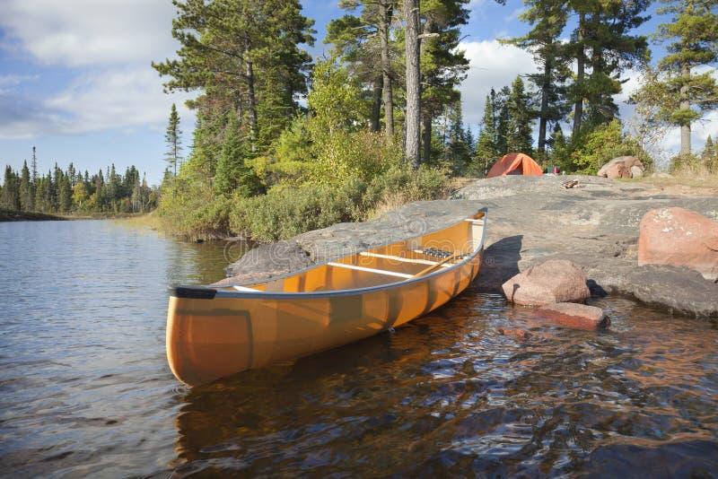 Campingplats och kanot på stenig kust av sjön royaltyfri bild